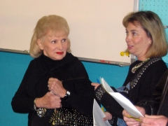 Eleanor Mauer (left) confers with an auction attendee while watching the event.