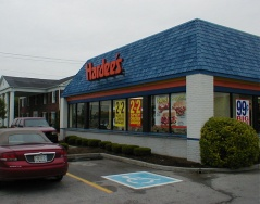 "This building has undergone the architectural changes that were typical when Hardees converted a store: the pitched roof is covered with shingles to form a larger, smooth-sloped roofline, and the walls are moved outward to form a larger, cleaner look. The original corner walls can be seen behind the ""99c Big..."" sign."