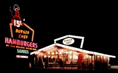 A postcard showing a nightime picture of the first store design. Notice the hamburgers were 15 cents each. [Click for larger picture]