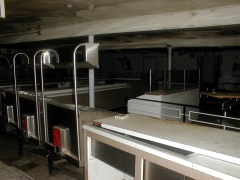 Behind the serving counter, and the restrooms can be seen on the back wall. An 8-track tape is on the counter.