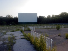 Facing the screen for Theater 1, looking over the concrete outdoor dining patio on this end of the concession stand.