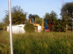 Photo of the playground area and a white storage shed.