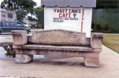 A bench made from the doorway arch stone from the original Farmers State Bank sits on the Northwest corner of Camelot Square. The large cube behind it is the original bank vault.