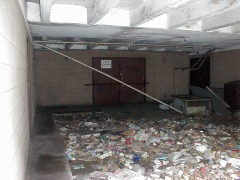 The trash-strewn loading dock. Not even vagrants will take refuge here.