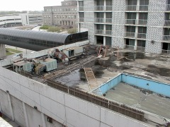 The rooftop swimming pool, with only a broken swingset and railing left.